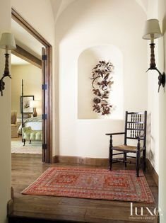 An intricately detailed iron sculpture by Joe Walters, purchased at Costello- Childs Contemporary, depicts a pair of birds fluttering near their nests. Ogden hung the piece, which appears suspended in air, in an arched niche just outside the master bedroom.