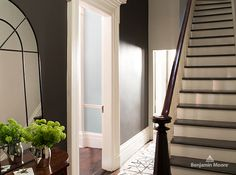 Rich brown walls layer luxe drama into a hallway and contrast beautifully with crisp white trim and stair risers. A mirror offers a bit of sparkle. | Wall colour, Mink (2112-20), Benjamin Moore Regal Select Waterborne Interior Paint; trim and ceiling colour, Soft Chamois (OC-13), Benjamin Moore. | #paint #decor