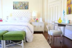 Lucite chair, green stools, white headboard.