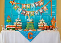 Train Party:  banner, plate background, poms + balloons, popcorn boxes, suitcases, apothecary jars