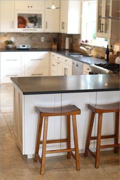 white kitchen cabinets, dark countertop, light tile floor