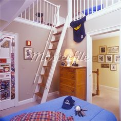 Muppet/CHILDRENS BEDROOMS - Boys room with a loft, beige walls, white trim and railings, steep stairs go up to loft, smallest room in house. Baseball gear on bed. Stock Photos