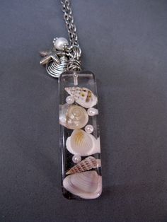 This listing is for a necklace containing real seashells and faux pearls in jewelers grade resin. The pendant was created by layering the items within a mold to create a rectangular shaped pendant. I then wrapped silver tone wire through a hole in the disc to make the bail. The pendant is accompanied by a starfish charm, a shell charm and a glass hand wrapped faux pearl bead. It would make the perfect gift for the beach lover!  The pendant measures about 2 long by 5/8 wide and about 1&#x...
