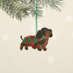 """This adorable little daschund is just waiting to be adopted! Hand-felted by artisans in Nepal, this darling daschund sports big, floppy ears, black bead eyes, and a hand knitted coat. Buy more than one to build your own pack! Comes with attached hanging loop. Dimensions: 2 1/2""""h. Holiday Gifts, Holiday Decor, Daschund, Knitted Coat, Green Gifts, Gift Certificates, Build Your Own, Gift Baskets, Nepal"""