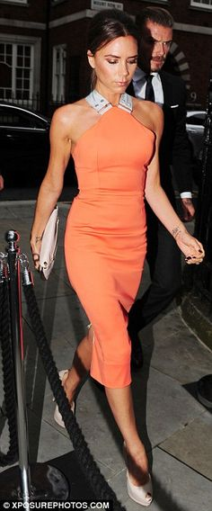 Deja vu: The designer wore a nude version of the dress in May ... Victoria Beckham looks long and lean in tangerine as she steps out in one of her most popular designs