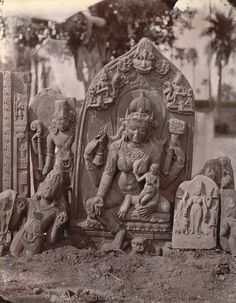 Photograph of a statue of a four-armed goddess with child and other fragments of sculpture from Rajaona, Munger District, taken by Joseph David Beglar around 1871-72.
