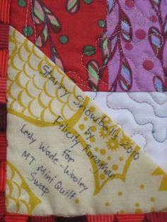 Easy way to attach a label - fold a square diagonally, and catch 2 sides of it in the binding.