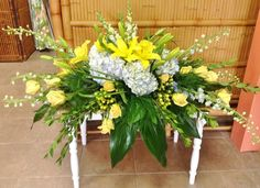 casket spray with blue and yellow flowers