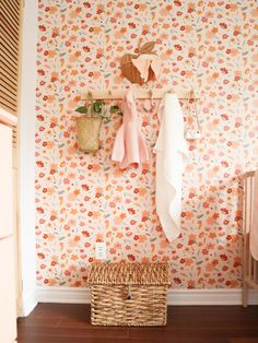 Prettiest baby girl nursery with a floral wallpaper, peg rails with a plant hanging and baby stuff, complete with a wicker toy trunck.