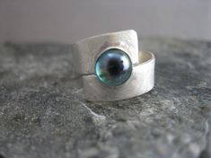 This ring is a wrapped brushed sterling strip, 1/4 inch wide, that is soldered at the center and topped with a beautiful 6mm rainbow topaz cabochon in a bezel setting. The rainbow topaz is a chameleon-like stone that has shades of blue, green, and violet to complement a wide range of