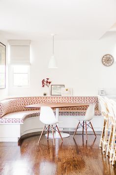 Family breakfast nook with patterned booth, modern table and chairs, and small clock
