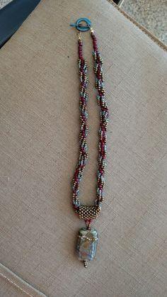 "Lamp worked glass, copper enamel clasp, 19"" long"