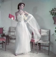 42-18018101    ca. March 1, 1952 --- Model wearing white strapless ballgown with long gloves, stole with daffodil corsage, and a red clutch, by Christian Dior. --- Image by © Condé Nast Archive/Corbis