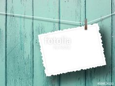 Close-up of one blank postcard frame hanged by peg against aqua wooden background