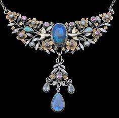ARTHUR GASKIN 1862-1928 &  GEORGIE GASKIN 1866-1934  Blue Bird Pendant  Silver Gold Black Opal Pink Tourmaline Opal Opal  Pendant: H: 6 cm (2.36 in)  W: 6.5 cm (2.56 in)   Chain: L: 32 cm (12.6 in)   British, c.1909
