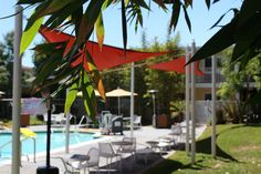 Red and yellow awnings create a calming yard. Palms Hotel, Calming, Oasis, Bungalow, Yard, Island, Yellow, Create, Outdoor Decor