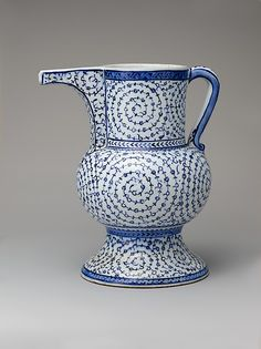 Ewer with 'Tughra-Illuminator' Style Decoration Date: 1525–40 Geography: Turkey, Iznik Culture: Islamic Medium: Stonepaste; painted in blue under transparent glaze
