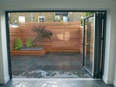 Modern minimalist garden design London, slate paving tiles, cedar wood timber privacy screen trellis, slate chippings, sleak calm modern urban living Contact anewgarden for more information Garden Privacy, Privacy Screen Outdoor, Wooden Gate Designs, Wooden Gates, Courtyard Landscaping, Cedar Cladding, Minimalist Garden, Modern Minimalist, Hardwood Decking