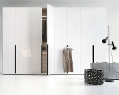 Lema's Flago is a modular wardrobe, shown here with hinged doors in glossy white lacquer and large vertical handles. Part of Al Centimetro, Lema's modular wardrobe system, Flago is also available matte lacquer, wood (heat-treated oak, charcoal stained oak, tobacco stained oak), glass, or a mirrored finish. The interior can be finished in numerous luxurious treatments, including a linen-like finish, Lino, shown here.