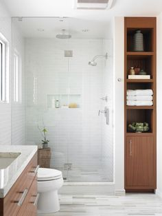 Sleek bathroom uses innovative storage to rid of clutter, including wooden shelves and cabinets, white glass subway tile in the shower and unique floor tiling | Beth Kooby Design