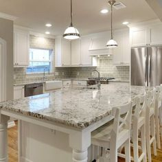 Bianco antico counter with grey Ann Sacks tile and white shaker cabinets.