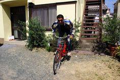 赤い自転車にまたがり疾走するスカジャンの男(フリー)