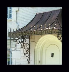 Custom made, decorative antique copper awning with wrought iron scroll brackets.