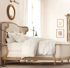 RH's Josephine Bed:A reproduction of a 19th-century French antique, our bed recalls the stately beauty of Louis XVI design, its feminine lines, exposed wood frame and camelback headboard with extended wings. Crafted of weathered solid oak, it features hand-carved rosettes and scrolls, and is richly upholstered in sand Belgian linen.