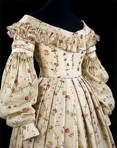 1830s extant gown, ruffles on neckline, collapsed sleeves.