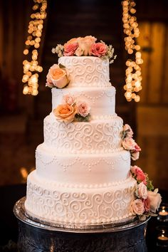 Gorgeous, white, five-tier, circle wedding cake with simple embellishments and peach//coral floral touches.  Simply stunning!  Taken at THE SPRINGS in New Braunfels, TX by Matt Montalvo Photography.