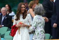 Smiles all round: Kate clutches her wicker clutch bag and red pashmina as she chats to a fellow guest 2 July 2014