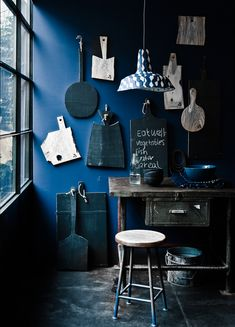 dark blue wall is a dramatic backdrop to a collection of natural wood and black painted cutting boards | 79 Ideas