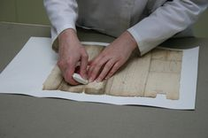 A conservator mechanically cleaning a document