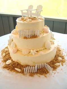"Buttercream icing with white chocolate seashells. The fence and chairs are not edible. Brown sugar around the base for ""sand"""