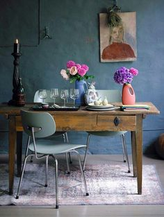 Old wooden desk as a table. Retro dining chairs and beautiful flowers.