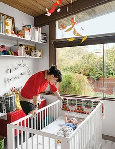 """Baby Max's bedroom (in his parents' Los Angeles A. Quincy Jones house) is outfitted with a Gulliver crib and a red PS cabinet, both from Ikea, as well as a Birds in Harmony mobile by Christel Sadde and Katsumi Komagata for the Museum of Modern Art Store. The custom """"I brake for unicorns"""" neon sign is from Let There Be Neon, a shop in New York City."""