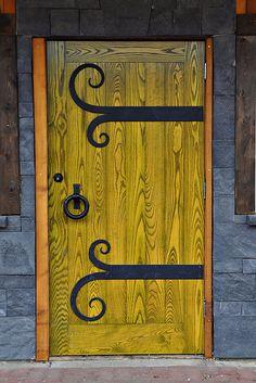 Yellow Door with decorative strap hinges