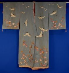 768 JAPANESE EMBROIDERED SILK FAILLE KIMONO, 1920s Pale blue lined in pink silk with satin stitch embroidered flowering cherry branches and flying cranes. Length 62. Pink padded hem shattered, lining stained, scattered pin holes, good. $575.00