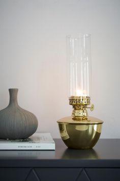 Dekorativ ljuslykta för värmeljus i form av en klassisk oljelampa. Av metall med avtagbart glasrör. Ø fot 11 cm, Ø glasrör 6 cm. Total höjd 27 cm.