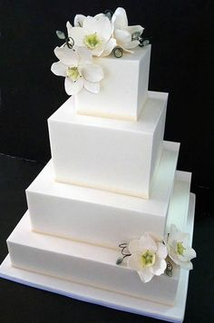 Sugar orchids with black curls adorn a sleek square cake for a stylish and modern confection.