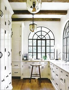 Wonderful black & white kitchen ~ and look at the reflections in those light fixtures! by Magic!