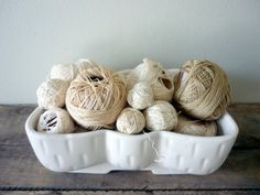 I just bought a big box of these vintage skeins all in the color of the large one on the right and love the way they are displayed here in a big white container. Lovely combination.