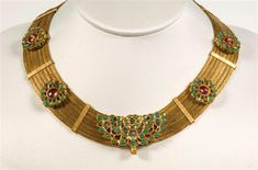 India, Rajasthan, Bikaner, 19th century. Provenance: A gold necklace decorated with 4 rosettes, each set with turqoises and spinelles, the centrepiece set with turqoises and white sapphires.