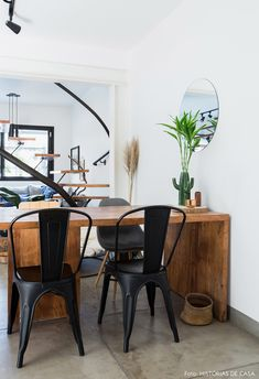 Sala de jantar com mesa de madeira e cadeiras de diferentes modelos, incluindo Eames e Tolix.