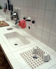 Built in trash disposal on a counter and a smoothly curved kitchen sink all tiled by DTile.