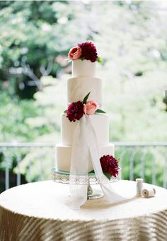 Simple elegant weffing cake with fresh fowers and lace.