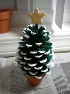 Paint the pine cone green; dip the tips in glue and sprinkle with glitter; glue the pine cone to the terra cotta pot and the star to the top of the pine cone.