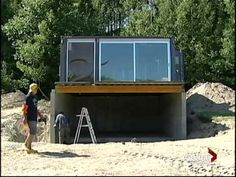 Garage under main living quarters with another container to right with stairs and storage and laundry