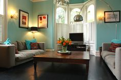 Dig the color/style mix here. Esp. the arc floor lamp, half shutters, funky pillows, blue walls, and arched windows