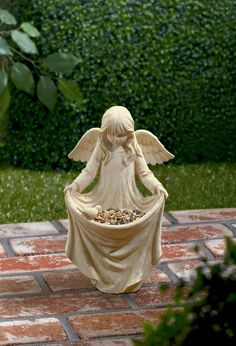 Such an adorable little angel statue holding her skirt to feed the birds